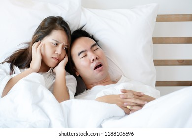 Couple on bed with white mattress Man snoring loud makes women feel annoyed. Causes Of Obstructive Sleep Apnea Stroke Chronic depression Sexual dysfunction It can be a cause of divorce in a spouse.