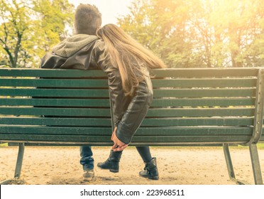 Couple on a bench - Two lovers sitting on a bench in a park and holding themselves by hands - Concepts of autumn,love,togetherness,relationship