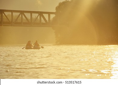 Couple on the boat and canoe floating on the river under old bridge in beautiful sunrise gold light.