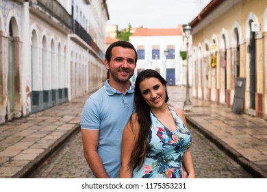 Couple on cobbled street smiling to camera in a historic city