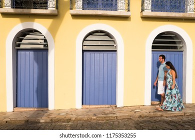 Couple on cobbled street with yellow wall and blue doors in a historic city