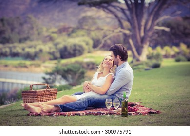 Couple on date looking at each other lying on a blanket