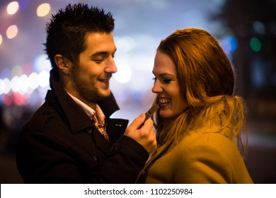 Couple on date - man feeds her girlfriend with chocolate in street at winter night