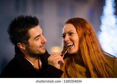 Couple on date - man feeds her girlfriend with chocolate in street at christmas season