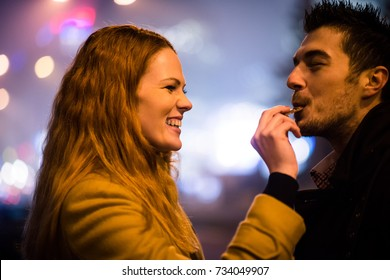 Couple on date - woman feeds her boyfriend with chocolate in street at winter night