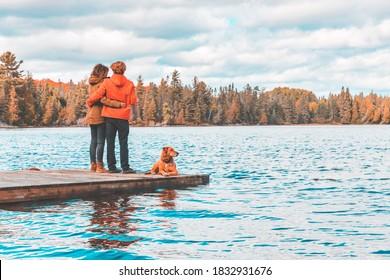 Coupé auf dem Dock mit Hund, Blick auf - Rückblick auf eine Frau und einen Mann umarmen und Blick auf den See in Kanada - Natur- und Lifestyle-Konzepte im Herbst