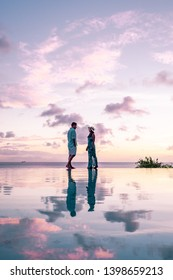 couple on the edge of an infinity pool watching sunset at the tropical beach of Saint Lucia or St Lucia Caribbean