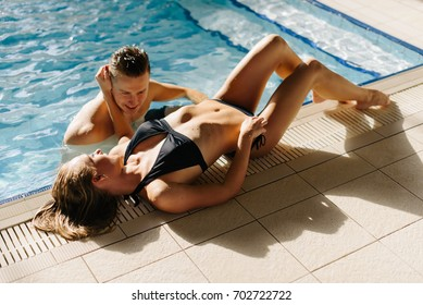 couple on the edge of the pool in luxury hotel.Sexy girl watered her hair and put hand on the man's head. Man and woman hugging, talking and smiling looking in eyes of each other