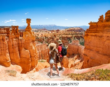 Couple on hiking trip looking at beautiful  mountain landscape,  Friends  relaxing on top of the mountain.  Bryce Canyon National Park, Utah, USA