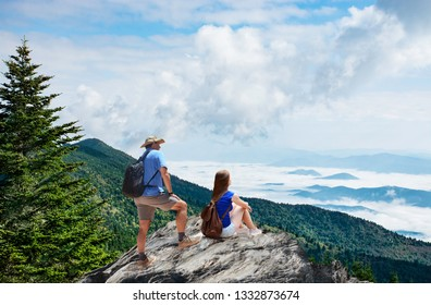 Couple on hiking trip, standing on top of the mountain over the clouds, enjoying beautiful summer mountain scenery. People enjoying beautiful view. Close to Asheville, North Carolina, USA.
