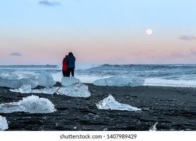 Couple on the Jokulsarlon beach. Iceberg from the famous Jokulsarlon Iceland. Glacier lake in Iceland.