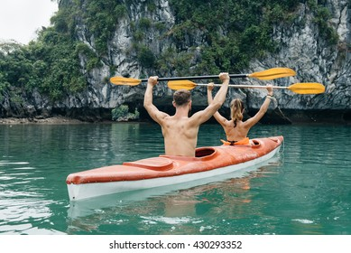 Couple on kayak celebrating success in Halong Bay. Front view on limestone island with azure water of Ha Long, Viet Nam.