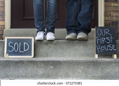couple on new home doorstep with sold sign and first house sign