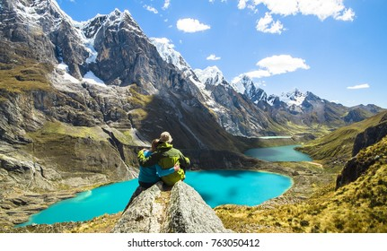 A couple on an overnight trek in the Peruvian Cordillera Huayhuash stops to admire the scenery.