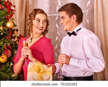 Couple on party near Christmas tree drink champagne and take gift box and Xmas presents.