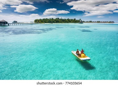 Couple on a pedalo boat is enjoying the turquoise waters of the tropical Maldives