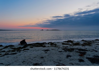 A couple on Plage Sainte-Marguerite are silhoueted by the reamins of a setting sun as sea mist creaps across the horizon