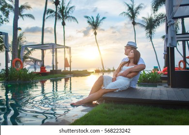 Couple on the pool at tropical resort travel concept