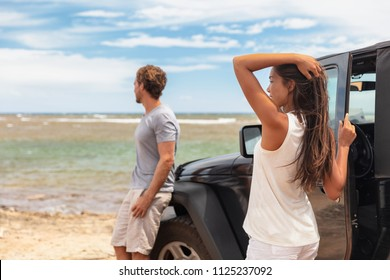 Couple on a road trip travel holiday in Hawaii driving car on beach. Young people tourists enjoying vacation.