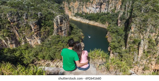 Couple on a rock overlooking a canyon with a river on the bottom and rocky walls covered by green trees. Furnas Canyon is a common tourist destination in Brazil