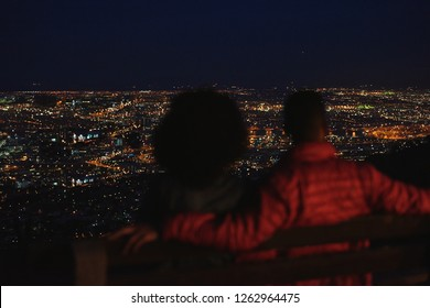Couple on romantic date, watching city lights from viewpoint at night
