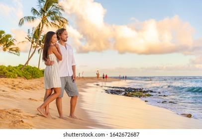 Couple on romantic sunset beach walk relaxing during Hawaii summer travel vacation on Kauai island, USA. Asian woman in white dress, Man in linen shirt.