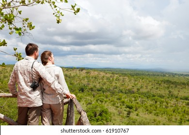 Couple on safari vacation looking to savanna from balcony
