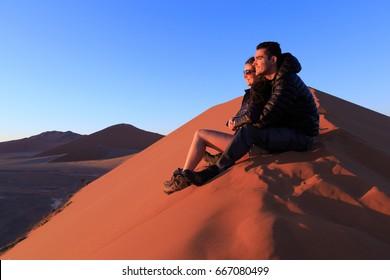 Couple on sand dune in desert during sunrise.  Sossusvlei, Namib Naukluft National Park, Namibia
