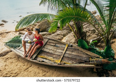 Couple on the shore of Paradise island. Couple in love on the seaside drinking coconut. Man and woman drink coconut. Honeymoon trip. Lovers on the beach. Wedding travel. Holiday romance. Sea tour