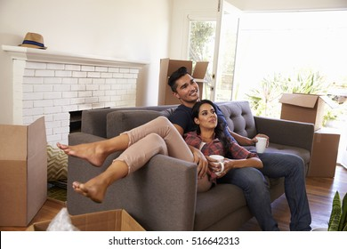 Couple On Sofa Taking A Break From Unpacking Watching TV