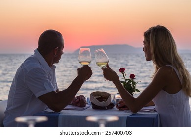 Couple on summer vacation drinking wine in sea restaurant at sunset