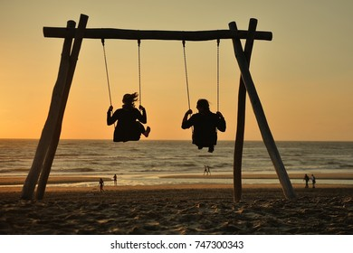 The couple on the swings watch the sunset