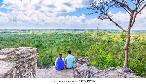 Couple on the top of Coba pyramid watching the mexican jungle
