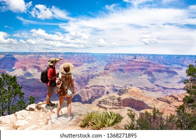 Couple on top of the mountain, looking at beautiful summer mountain  landscape. Friends on hiking trip enjoying view of Grand Canyon. South Rim. Grand Canyon National Park, Arizona, USA.