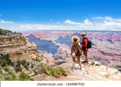 Couple on top of the mountain, looking at beautiful summer mountain  landscape. Friends on hiking trip enjoying view of Grand Canyon. South Rim. Travel in Grand Canyon National Park, Arizona, USA.