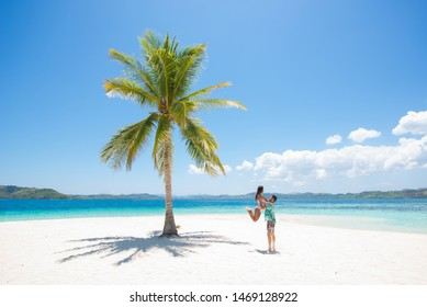 Couple on a tropical beach with blue water and palm trees - Coron, Philippines