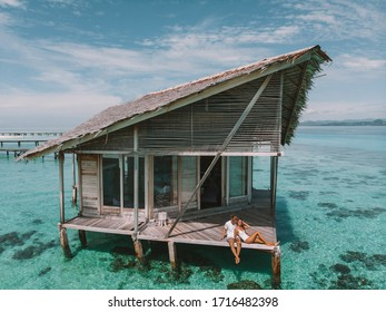 Couple on a tropical beach jetty at Maldives enjoy honeymoon in tropical wooden water bungalow. Couple enjoying morning vacations on tropical beach bungalow looking ocean view