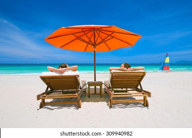 Couple on a tropical beach relax in the sun on deck chairs under a red umbrella.  Travel  background.