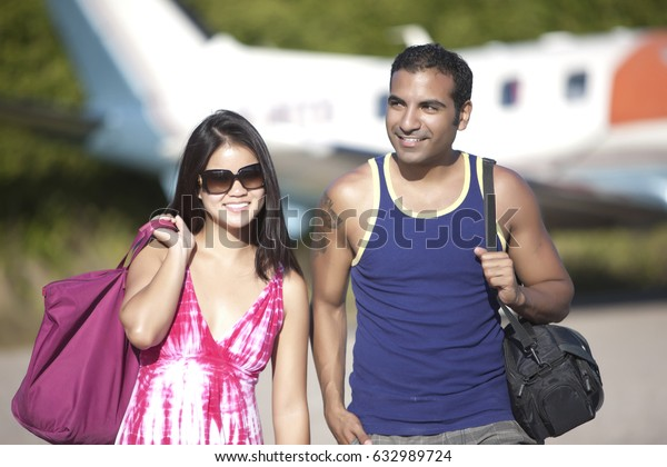 Couple on vacation leaving airplane