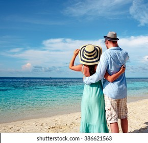 Couple on vacation walking on a tropical beach Maldives. Man and woman romantic walk on the beach.