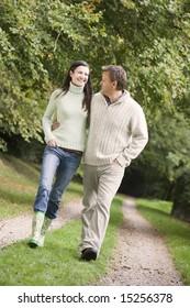 Couple on walk along woodland path in autumn