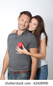 Couple on white background holding red hearts