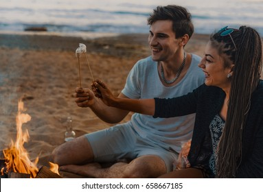 Couple on a wild beach lit a bonfire and fry marshmallows. Sunset time