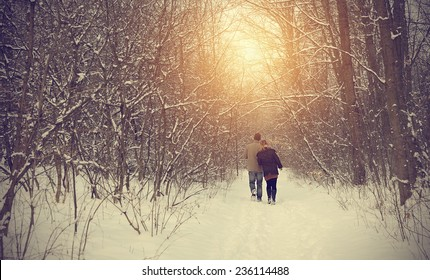 Couple on winter path in forest on a sunny day