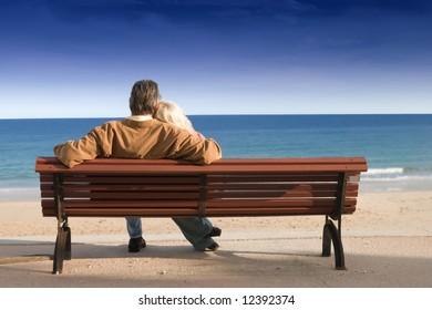 Couple on wooden bench looking out to sea