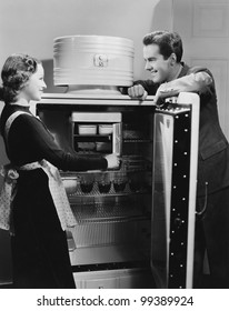 Couple with open refrigerator