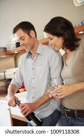 Couple opening up bottle of wine