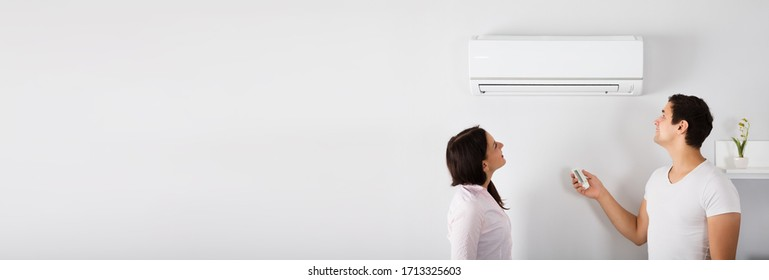 Couple Operating Air Conditioner In Living Room At Home