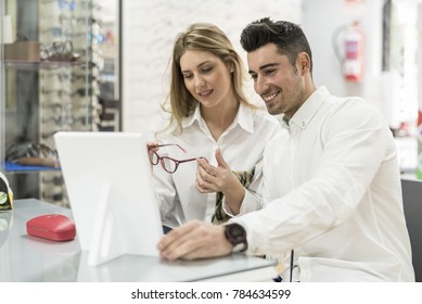 Couple in optician glasses store trying on models with mirror