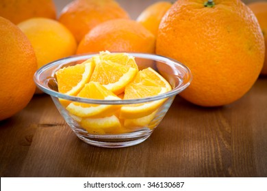 Couple of orange slices in a glass bowl, on a wooden surface with whole oranges in the background
